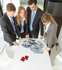 Meeting with people around a table with a white puzzle with a red piece standing apart