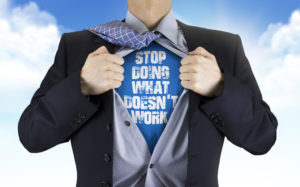 businessman showing Stop doing what doesn't work words underneath his shirt over blue sky