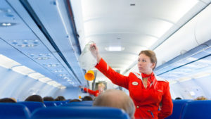 44088939 - moscow - may 28, 2011: air hostess yulia of aeroflot shows how to use an oxygen mask on board. aeroflot operates the youngest fleet in the world among major airlines, numbering 150 airliners.