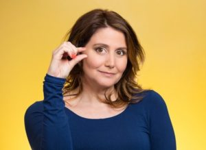 31160090 - closeup portrait, young middle aged woman, showing small amount gesture with hands, isolated yellow background. human emotion facial expression feeling, body language, sign, symbol, reaction, perception