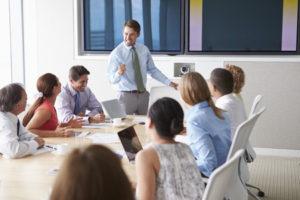 42314252 - motivational speaker talking to businesspeople in boardroom